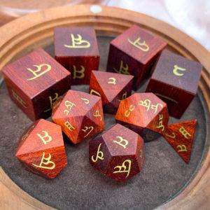 Artisan Dice - Bloodwood with Elvish Brass Inlay in Rambutan Reliquary